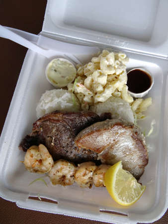 Surf & Turf Includes: Ahi, Steak, Shrimp, rice, and macaroni  salad with small cups of sauce, lemon in a styrofoam tray with plastic knife and fork. photo