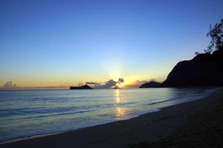 windward: Early Morning Sunrise on Waimanalo Beach on Oahu, Hawaii over Rock Island bursting through the clouds.  January 2013.