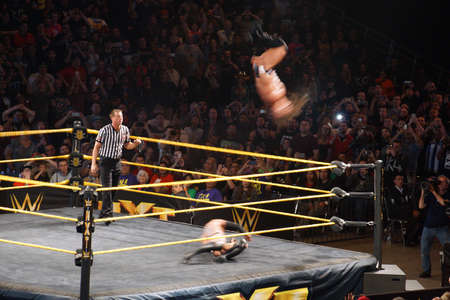 punch press: SAN JOSE - MARCH 27: NXT male wrestler Adrian Neville flips in the air as he performs the red arrow as Finn Baylor rolls out of the way undernearth during match at the San Jose Event Center in San Jose, California on March 27, 2015.