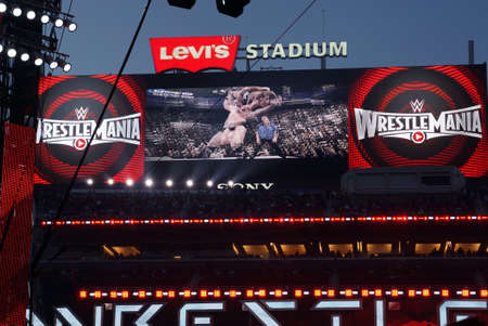 hdtv: SANTA CLARA - MARCH 29: Sony HDTV big screen scoreboard shows clip of Brock Lesner F-5ing the Rock from Summerslam during the showcase of the immortals, Wrestlemania 31, as night falls at the Levis Stadium in Santa Clara, California on March 29, 2015. Editorial