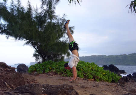 Man wearing a hat, t-shirt, pants, and slippers Handstands on Rocky shore with Kainalimu Bay in the background on Maui, Hawaii photo