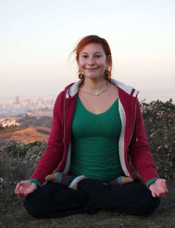 Beautiful Lady sits smiling in seated meditation with San Francisco in Background.