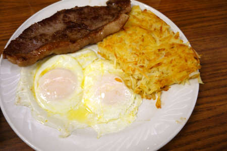 Steak ribs with two eggs over easy, Hash-brown potatoes and on a plate on table. Stock Photo