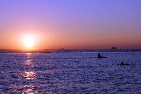 oceanscape: People and boats in the water during Sunset over the ocean at Ala Moana Beach Park on Oahu, Hawaii.