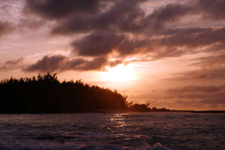 watery: Sunset through the clouds and over the trees as it reflects on the watery waves at Kawela Bay on the North Shore of Oahu. Stock Photo