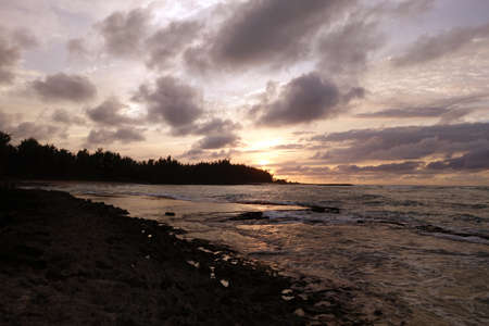 watery: Sunset through the clouds and over the trees as it reflects on the watery waves at Kawela Bay rocky shore on the North Shore of Oahu.