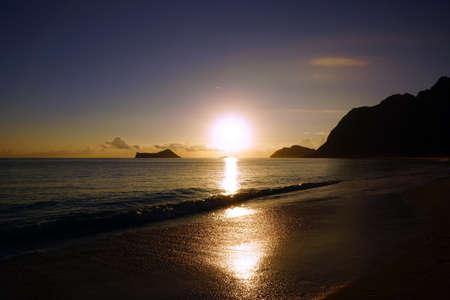 windward: Early Morning Sunrise on Waimanalo Beach on Oahu, Hawaii over Rock Island bursting through the clouds. 2013.
