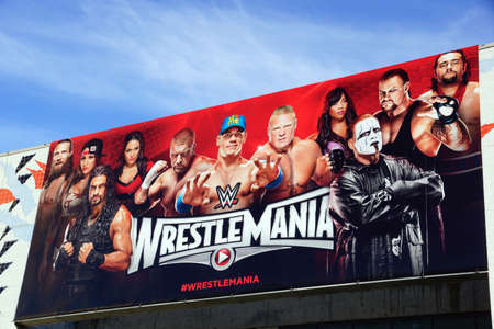 wrestlers: SAN JOSE - MARCH 28: Wrestlemania 31 poster sign on side of McEnery Convention Center building featuring WWE Wrestlers like John Cena, Triple H, Brock Lesner, Undertaker, Rusev, Daniel Bryan, Roman Reigns, Daniel Bryan, Bella sisters, and Alicia Fox for F