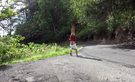 Man wearing a hat, t-shirt, shorts, and slippers Handstands at Tantalus Mountain road with lush vegetation above the City of Honolulu on Oahu, Hawaii