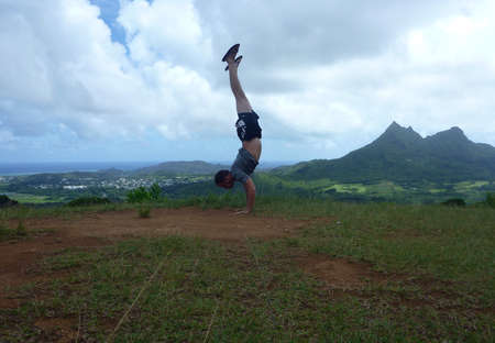 windward: Man Handstands at Pali Highway lookout point wearing t-shirt, basketball shortes, and slippers with Kailua and Windward Oahu visible.