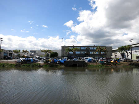 encampment: HONOLULU, HI - JUNE 4, 2015: Homeless tents and cars parked along the Kapalama Canal in Honolulu, Hawaii.  The Kapalama Canal has been the site of a recent homeless encampment in Honolulu. Editorial