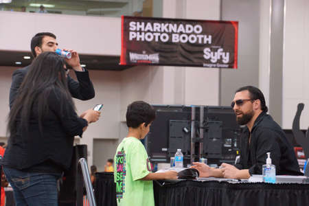 san jose: SAN JOSE - MARCH 28: Damien Sandow talks to kid fan as mom takes photo on cellphone and he signs magazine at WWE Axxess event at the McEnery Convention Center in San Jose, California on March 28, 2015. Editorial