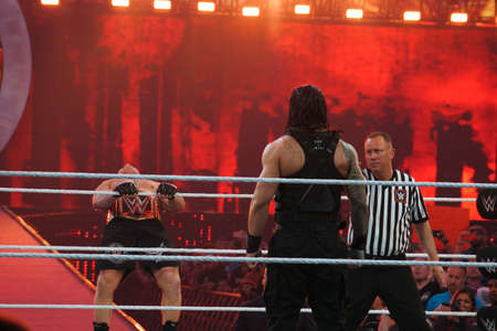 levis: SANTA CLARA - MARCH 29: WWE Champion Brock Lesner leans back as he holds rope as he enters ring with Roman Reigns standing in ring at, showcase of the immortals, Wrestlemania 31,with fans cheering and taking photo at the Levis Stadium in Santa Clara, Cal