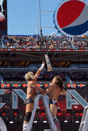 levis: SANTA CLARA - MARCH 29: Dolph Ziggler reaches for the Intercontinental championship belt as it hangs in the air with Daniel Bryan winds-up to punch him on top ladder during ladder match at Wrestlemania 31 with crowd in the distance at the Levis Stadium i