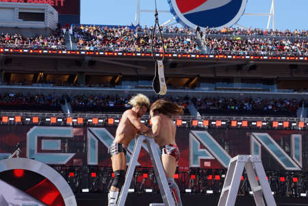 levis: SANTA CLARA - MARCH 29: Dolph Ziggler headbutts with Daniel Bryan with hair flying on top ladder for the Intercontinental championship belt as it hangs in the air with  during ladder match at Wrestlemania 31 with crowd in the distance at the Levis Stadiu