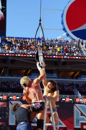 intercontinental: SANTA CLARA - MARCH 29: Dolph Ziggler and Daniel Bryan reaches for the Intercontinental championship belt as it hangs in the air with Dean Ambrose climbing towards them during ladder match at Wrestlemania 31 with crowd in the distance at the Levis Stadiu
