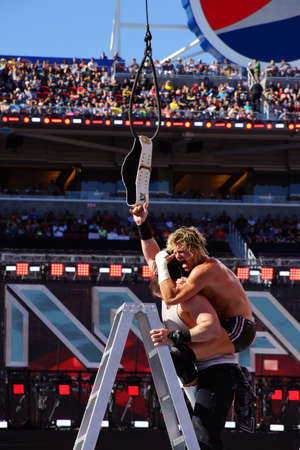 SANTA CLARA - MARCH 29: Dolph Ziggler gives sleeper hold to Luke Harper as he reaches for the Intercontinental championship belt as it hangs in the air during ladder match at Wrestlemania 31 with crowd in the distance at the Levis Stadium in Santa Clara,