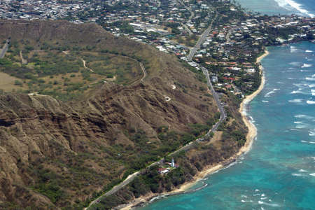 Aerial view of Diamond Head Crater, Lighthouse, Beach, Black Point and Kahala on Oahu with wave braking against ocean reef on nice day. March 2015.