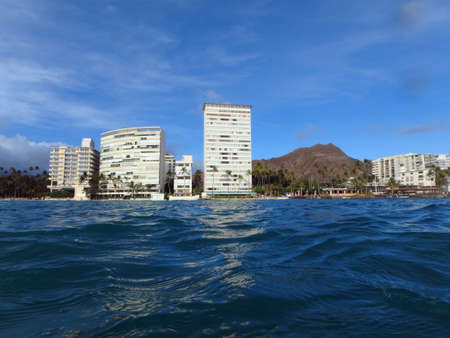 outrigger: Beach, Hotel building, Outrigger Canoe Club, coconut trees, Condo buildings, clouds, and Diamond Head Crater in the distance on Oahu, Hawaii viewed from the water on a beautiful day.