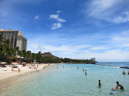 hang out: WAIKIKI - JUNE 16: People play in the water and hang out on the beach in world famous tourist area Waikiki on a beautiful day with Diamond head and hotels in the distance.  June 16 2015 in Waikiki, Hawaii.
