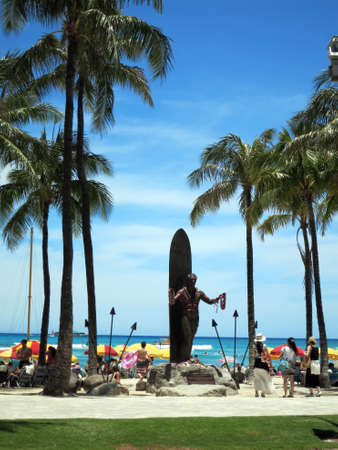 leis: HONOLULU - JUNE 16: Female tourist look at Duke Kahanamoku statue holding leis at Waikiki Beach on June 16, 2015. Duke is a legendary athlete of Hawaii and the ambassador of Aloha. Editorial