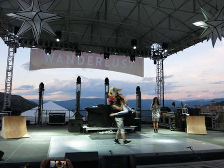 spins: SNOWMASS, CO - JULY 3:  Man spins lady in the air on stage during wanderlust spectacular concert with mountain landscape in background at dusk during Wanderlust festival at Snowmass Village area in Colorado on July 3, 2015.