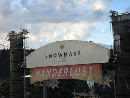 wanderlust: SNOWMASS, CO - JULY 2:  Snowmass Village Colorado and Wanderlust festival signs against a cloudy sky at Snowmass Village area mountains during festival in Colorado on July 2, 2015.