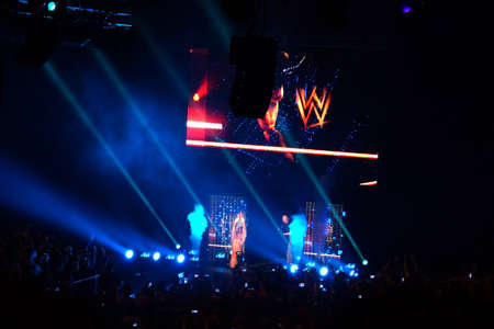 wrestlers: SAN JOSE - MARCH 27: NXT male wrestler Adrian Neville knells and points into the air as he makes his entrance for match at the San Jose Event Center in San Jose, California on March 27, 2015.