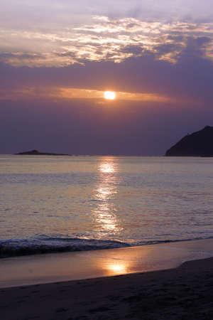 windward: Early Morning Sunrise on Waimanalo Beach over Rock Island a crack in the clouds on Oahu, Hawaii. Stock Photo