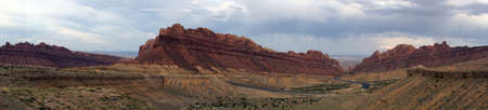 san rafael swell: Panoramic of Road winds through Spotted Wolf Canyon with dramatic clouds in sky in Utah, USA.
