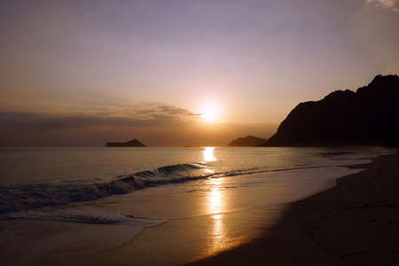 windward: Early Morning Sunrise on Waimanalo Beach on Oahu, Hawaii over Rock Island bursting over the clouds.