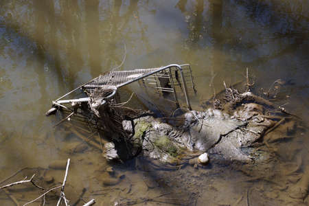 the river: Abandoned shopping trolley in muddy water with other junk. Stock Photo