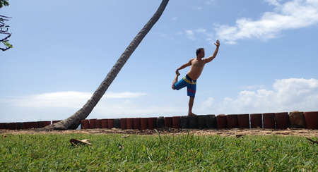 bathing man: Man wearing bathing suit does Dancer pose on seawall along tree pose. Stock Photo