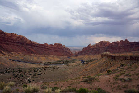 san rafael swell: Road winds through Spotted Wolf Canyon with dramatic clouds in sky in Utah, USA.