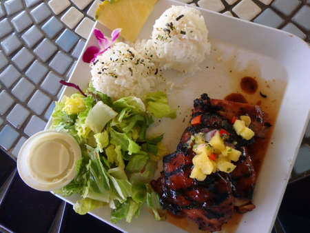 side salad: Hawaiian BBQ Chicken Plate guava marinated, pineapple-pepper sauce, White Rice, Pineapple slice, flower, and Salad with side of dressing on square white plate on a table. Stock Photo