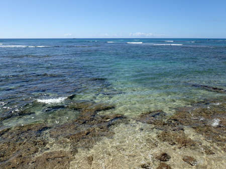 breaking in: Shallow ocean waters with coral and small waves breaking in the distance of Waikiki area looking into the pacific ocean. Stock Photo