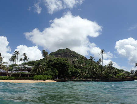 diamond head: Makalei Beach with waves lapping, napakaa, lava rock wall and Coconut trees with Diamond Head in the background along the shore on a wonderful day in Oahu, Hawaii.
