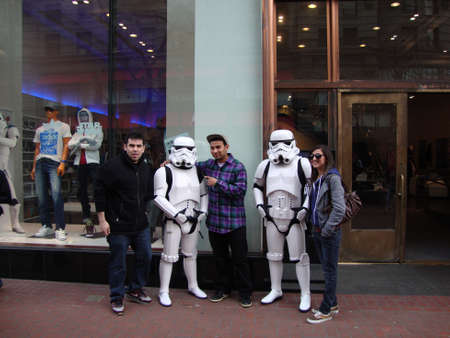 starwars: SAN FRANCISCO - JANUARY 16:  two guys and a women pose with Star Wars characters Storm Troopers in front of Adidas store in San Francisco on January 16, 2010. Editorial