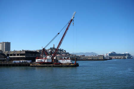 coit: SAN FRANCISCO - OCTOBER 11:  Crane on barge does Pier repair work with Coit Tower on top Telegraph hill and Cruise ship in the distance in San Francisco, California.  October 11, 2015.
