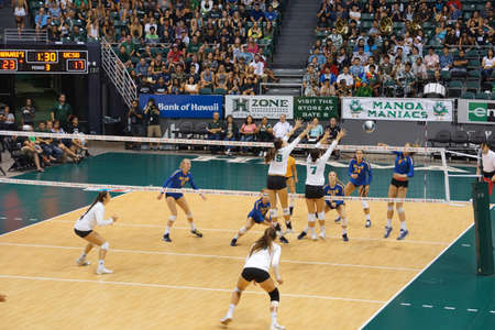women's volleyball game: HONOLULU, HI -  SEPTEMBER 25: UCSB player jumps to hit volleyball as UH Womens players jump to block Volleyball during game. September 25, 2015 Honolulu, Hawaii.