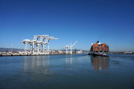 oakland: OAKLAND - OCTOBER 12: Fully loaded Shipping Cargo Boat pushed through harbor under giants unloading cranes in Oakland Harbor.  Oakland California on October 12, 2015.