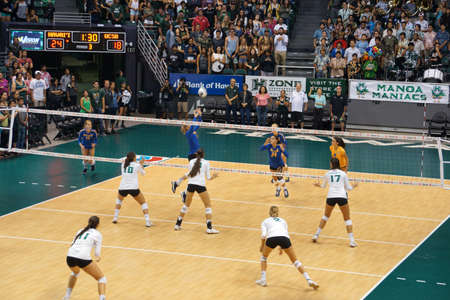 women's volleyball game: HONOLULU, HI -  SEPTEMBER 25: UCSB player volleys volleyball to teammate as UH Womens players set to block Volleyball during game. September 25, 2015 Honolulu, Hawaii.