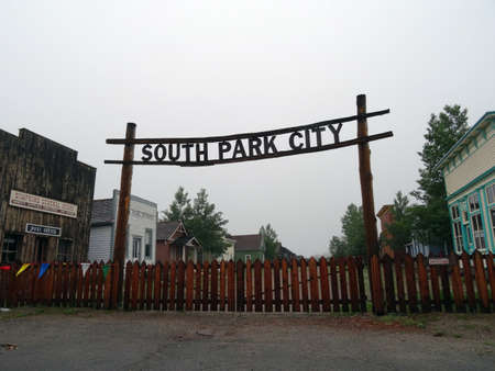 south park: SOUTH PARK CITY, COLORADO, JULY 7: Historic South Park City Sign hangs in the air above wood fence leading into replica town July 7, 2015 in Colorado.
