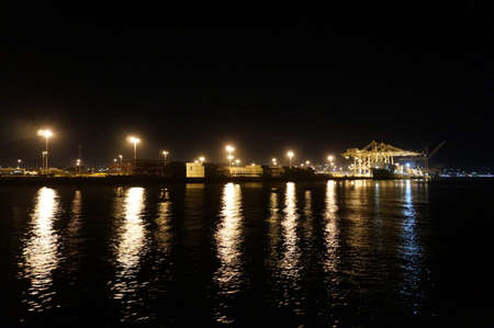 oakland: OAKLAND - OCTOBER 12: Fully loaded Shipping Cargo Boat unloaded at night under giants unloading cranes in Oakland Harbor with lights reflecting on the water and matson shipping containers on the shore.  Oakland California on October 12, 2015.