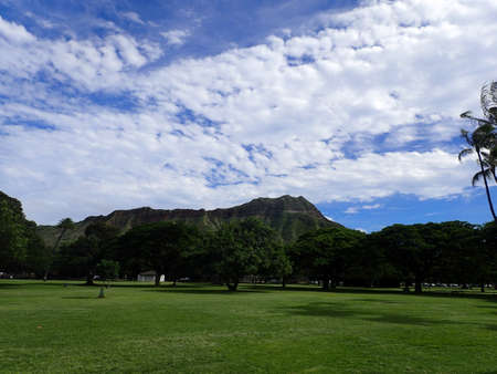 diamond head: Kapiolani Park at during day with Diamond Head and clouds in the distance on Oahu, Hawaii. Stock Photo