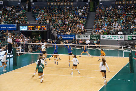 women's volleyball game: HONOLULU, HI -  SEPTEMBER 25: UH player jumps to hit volleyball as UCSB Womens players jump to block Volleyball during game. September 25, 2015 Honolulu, Hawaii.