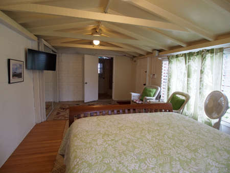 queen bed: Inside Cottage Bedroom with Queen bed, Mounted HDTV, White Wicker chairs and bathroom.
