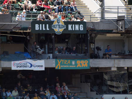 OAKLAND, CALIFORNIA - JUNE 23: Sportscasters call game from Xtra 860am Radio booth next to Comcast Sportsnet Videographer with Bill King Holy Toledo sign above them and fans in bleachers at As Baseball game at the Oakland Coliseum on June 23, 2010 in Cal Editorial