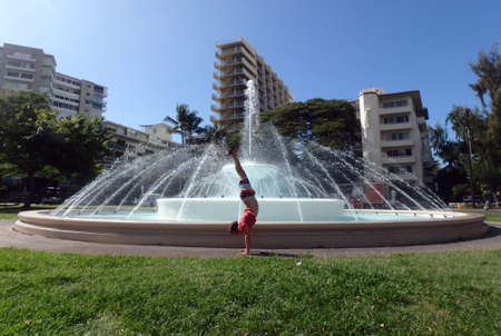 Man wearing t-shirt, swimsuit, slippers Handstands in front of Dillingham Fountain at Kapiolani Park Dillingham Fountain at Kapiolani Park is located across the street from the Elks Club at Poni Moi Street.  In the 1960s, the city constructed the fountain