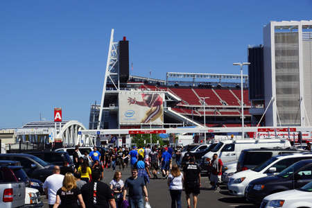 levis: SANTA CLARA - MARCH 29: People walking through parking lot to arena before the start of the showcase of the immortals, Wrestlemania 31, at the Levis Stadium with Intel 49ers ad on side of building in Santa Clara, California on March 29, 2015. Editorial